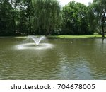 Small photo of Fountain in the middle of a pond in a park in Massillon, OH