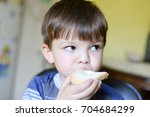 boy eating bread with cream... | Shutterstock . vector #704684299