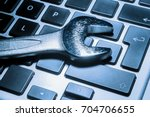 metallic wrench over a computer ... | Shutterstock . vector #704706655
