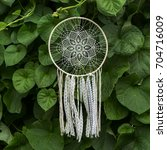 Small photo of ancient native american dream catcher with white handmade crochet doily