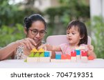 asian mother and daughter are... | Shutterstock . vector #704719351