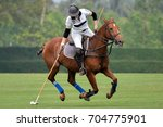 Stock photo woman horse polo player use a mallet hit ball in tournament 704775901