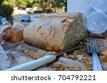 Small photo of some cut bread, a steel fork and some plastic cups in the park after a pic nic