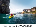 woman paddles kayak in the calm ... | Shutterstock . vector #704804041