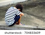 a sad boy sitting on the street ... | Shutterstock . vector #704833609