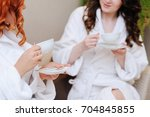 two young women drinking tea... | Shutterstock . vector #704845855