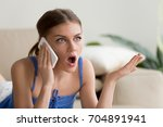 Small photo of Surprised young woman talking on mobile phone, confused after hearing unbelievable news on cellphone, shocked girl because of unexpected call. Abruptness, quarrel and affront during phone conversation