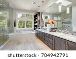 Small photo of Contemporary master bathroom features a dark dual vanity cabinet , glass walk-in shower, drop-in tub and open cabinets filled with shelves. Northwest, USA