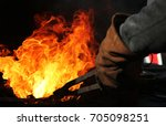 A  Blacksmith At Work With...