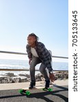 Small photo of Young mixed race man skateboarding, having fun passionate hobby summer carefree lifestyle