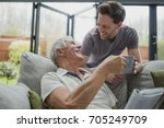 man is leaning over the sofa to ... | Shutterstock . vector #705249709