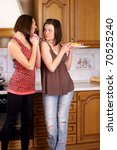 Two woman with croissant in the kitchen - stock photo