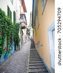 Small photo of Zurich, Switzerland - August 9, 2007: Downtown city with empty narrow street and alley by residential apartment buildings with incline and steps