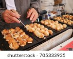 Small photo of cooking takoyaki a kind of Japanese traditional snack served as ball shape coat with mixed flour, vegetable, and octopus or tako