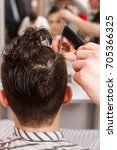 young man getting haircut by... | Shutterstock . vector #705366325