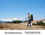 Small photo of Rearview of an adventurous man with hiking equipment using trekking sticks while walking the mountain copyspace travelling adventure nature landscape sport activity
