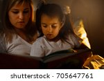 mother and child girl reading a ... | Shutterstock . vector #705647761