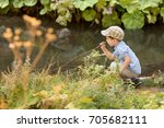 young boy playing near by a... | Shutterstock . vector #705682111