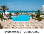Territory of the hotel with a swimming pool, a recreation area and the sea
