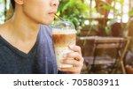 man drinking an iced latte... | Shutterstock . vector #705803911
