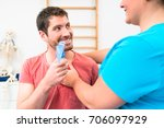 Small photo of Man taking pulmonary function test with mouthpiece in his hand in doctor office