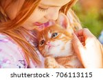 little girl with a red kitten... | Shutterstock . vector #706113115