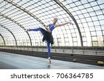 Small photo of Wonderful ballerina is posing on the railway station. She stands on the right toe with outstretched to the side left arm and left leg and looks upward. Girl wears a blue dance wear with a black tutu.