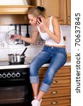 Young attractive woman cooks soup while talking by phone - stock photo