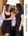 Two young beautiful women talking about something in the home kitchen with wine glasses - stock photo