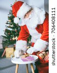 Small photo of santa claus stealing cookies and glass of milk from table