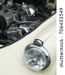 Small photo of old white car with the engine visible though open hood with headlamp alternator and air filter visible