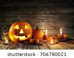 Stock photo halloween pumpkins and candles on wooden 706780021