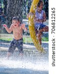Small photo of happy boy laughing and cooling off in a summertime splash pad
