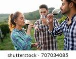 people tasting wine in vineyard | Shutterstock . vector #707034085