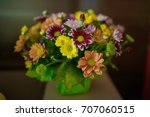 Small photo of Varied colors blossoms in a rustic bridal arrangement positioned against a dark background. Wedding arrangements, floral setting and ideas for bride morning preparation.