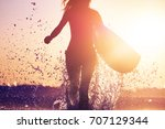 woman with surfboard runs from... | Shutterstock . vector #707129344