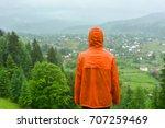 man in an orange raincoat on...   Shutterstock . vector #707259469