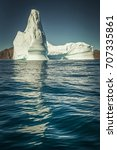 Small photo of Towering iceberg afloat in Greenland with reflection in water, a symbol of the strength of the environment and the challenges of climate change