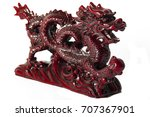 Small photo of Wealth and power symbolized by the fengshui styled mystic dragon red statue with a clipping path. Feng Shui is a Chinese philosophical system of harmonizing everyone with the surrounding environment