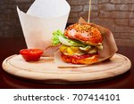Small photo of hamburger with souse and fries on the wood plate - studio photo