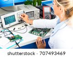 Small photo of Young attractive female electronic engineer using digital oscilloscope in the laboratory