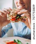 man eats a big sandwich with... | Shutterstock . vector #707753809