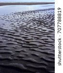 Small photo of Wave pattern in sand by receding tide pool on coastal beach in the Pacific Northwest, with digital color filter, for motifs of alteration, transience, or periodicity in nature