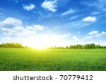 bright sunset over green field. | Shutterstock . vector #70779412