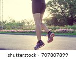runner feet running on road at