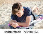 Teenage boy laying on a beach using a mobile phone - stock photo