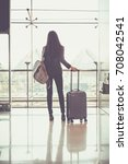 Small photo of Airport woman holding disposable cup of coffee in hand at gate waiting in terminal. Air travel concept with young casual business woman sitting with carry-on hand luggage trolley.
