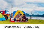 Small photo of Group Asian of man and women have friendship enjoy camping for picnic and barbecue at lake with tents on background; travel concept and happy family.