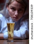 Small photo of Closeup portrait of young drunken female sitting at the table with beer glass. Woman looking at the camera. Alcohol addiction.