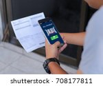 Small photo of Mobile bill payment barcode scan concept.Man hands using mobile phone and holding bills